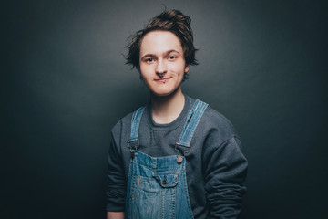 Portrait of smiling young man wearing denim overalls over gray background