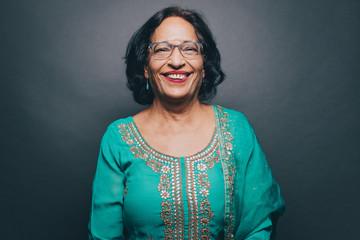 Portrait of smiling senior woman wearing salwar kameez on gray background