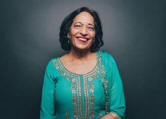 Portrait of smiling senior woman wearing salwar kameez against gray background