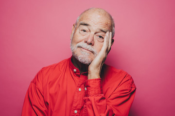 Portrait of bored senior man with head in hand against pink background