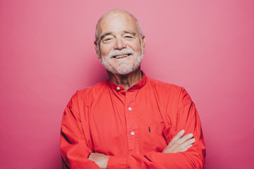 Portrait of smiling senior man with arms crossed against pink background