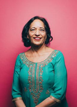 Portrait of smiling senior woman wearing salwar kameez against pink background