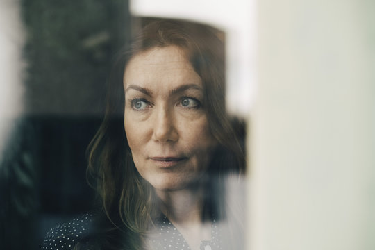 Portrait of mature woman looking out window