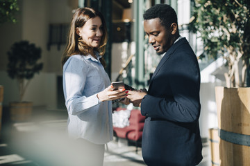 Businesswoman showing mobile phone to male colleague during conference
