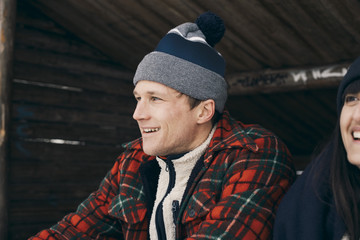 Close-up of smiling man and woman sitting in log cabin