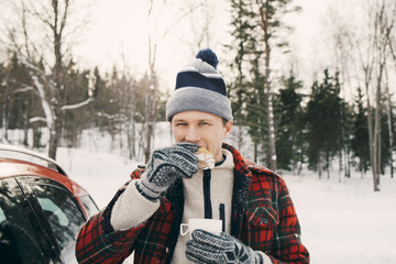 Man eating bread while having coffee in car trunk at park during winter