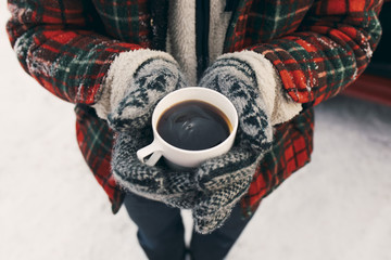 Person in winter clothes holding hot coffee
