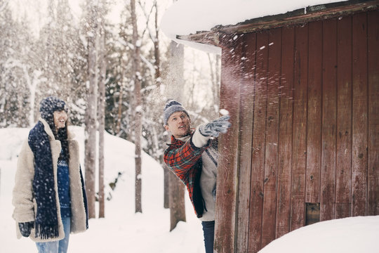 Friend looking at man throwing snowball while standing behind log cabin during winter