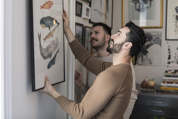 Two men hanging picture on wall