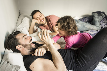 Cheerful fathers playing with daughter while lying on bed at home