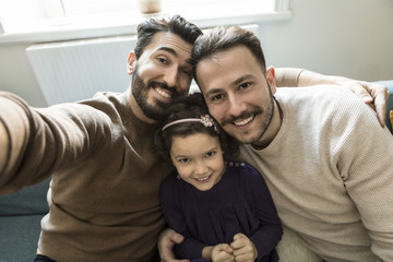 Smiling fathers and daughter taking selfie while sitting on sofa in living room at home