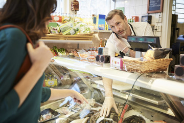 Male owner talking on mobile phone while picking up seafood from display cabinet for customer in store