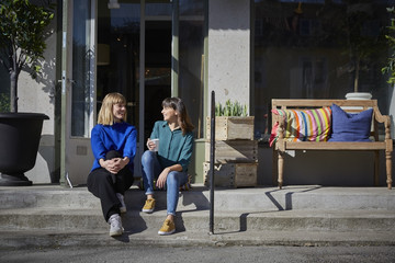 Full length of smiling owners talking while sitting on steps outside store