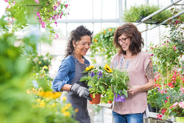 Gärtnerin und Kundin haben Spaß bei der Blumenauswahl im Gewächshaus
