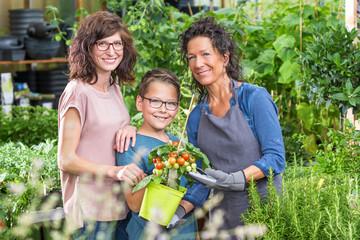 Mutter mit Sohn in der Gärtnerei beim Tomatenpflanzen kaufen
