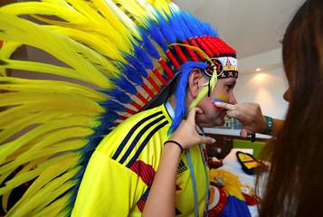 Columbian soccer team supporter Edgar Marquez has his face painted by Anna Maria as they prepare in their hotel room for their team's World Cup soccer match against Senegal at Samara stadium in Samara