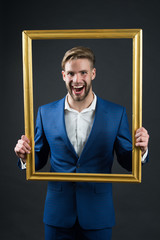 Happy man hold picture frame. Businessman smile through frame. Focus on me. Portrait of me. Family portrait. Catch the moment. Bride groom at wedding. Smiling and handsome