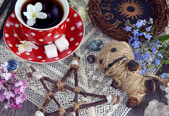 Voodoo doll with pentagram, cup of tea, mysterious objects and flowers. Occult, esoteric and divination still life. Halloween background with vintage objects and magic ritual