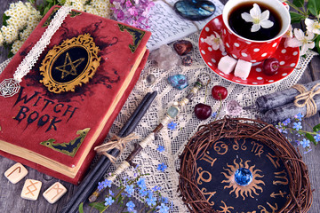 Witch book with magic spellings, black candles, flowers and cup of tea with zodiac circle. Occult, esoteric and divination still life. Halloween background with vintage objects and magic ritual