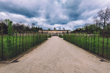 April, 14th, 2017 - Potsdam, Brandenburg, Germany. Picture Gallery also known as Bildergalerie in Sanssouci palace park. Historic building and spring trees alley by cloudy dramatic sky.