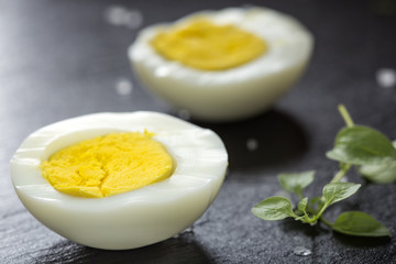Slices of boiled hard eggs on a dark slate with green oregano