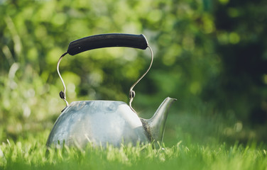 Old household utensils. A metallic teapot on the background of a green garden