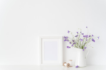 White portrait frame mockup with wild flowers in jar and silk ribbons near white wall. Empty frame mock up for presentation design. Template framing for modern art.