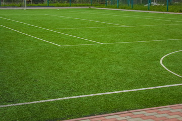 sport concept synthetic small football field green grass background texture and  white marking lane with empty space for copy or text