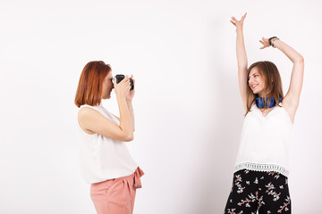 Woman photographer and her female friend taking pictures in studio over a white wall