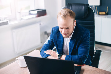 businessman uses a laptop and wireless headphones in the office. the manager is talking on the Internet.