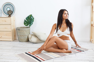 Charming young woman in beautiful gymnastic suit doing yoga exercises Marichiçana sitting on the rug in the morning