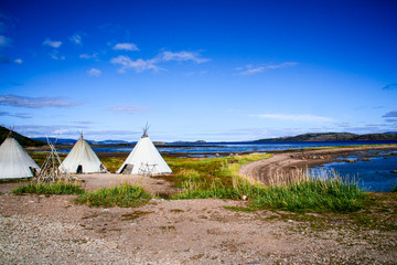 Three lavvu, or traditional lappish yurts (reindeer skin tents) used by the indigenous Sami people sit next to a lake in near Alta in the Finnmark region of northern Norway and Lapland on a summer day