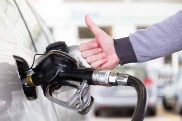 Petrol or gasoline being pumped into a motor vehicle car. Closeup of mans hand showing thumb up gesture, pumping gasoline fuel in car at gas station. Black and white image.
