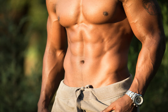 Abs and chest closeup of african macho man bodybuilder topless with naked torso