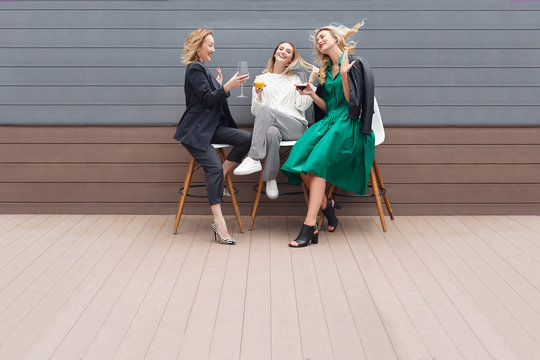 Three charming girls - friends blondes in stylish clothes drink alcoholic beverages and cocktails celebrate a bachelorette party on an open wooden terrace