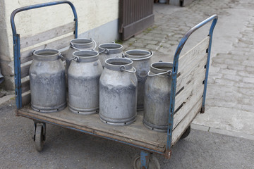 old, metal milk cans on trolley