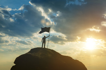Silhouette of a man on top of a mountain with the flag of victory. Against the background of the sky in the sunset. High achievements, success in business, leadership,