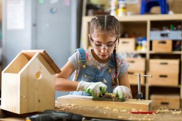 Girl building birdhouse in garage