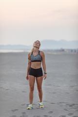 Sportswoman Stratching on Beach