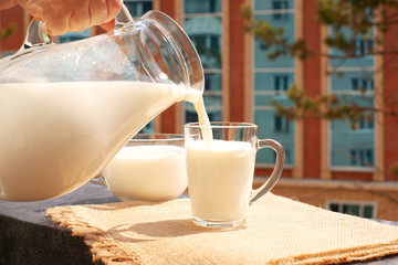 Milk is poured into a mug. Milk is poured from the jug into the mug for breakfast on the balcony sill.
