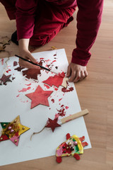Young child painting Christmas decorations kneeling down on the floor