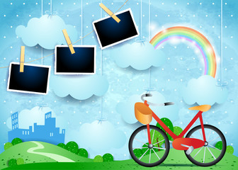 Surreal landscape with small city, bike and photo frames