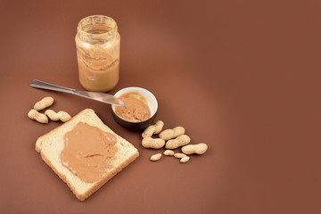 Toast with peanut butter stock images. Peanut butter on a brown background with copy space for text. Glass of peanut butter stock images. Breakfast still life. American delicacy