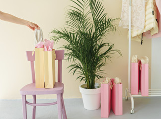 several paper shopping bags indoor. woman hand holding cloth