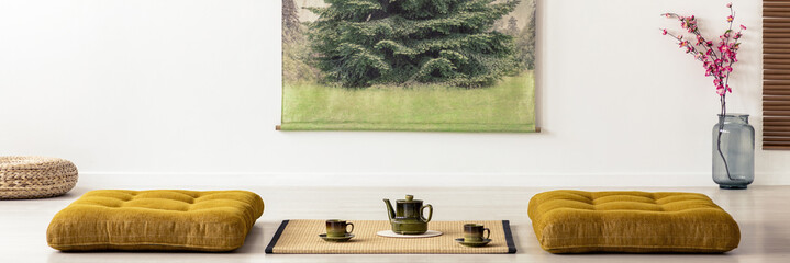 Kettle and cups on tatami mat between cushions in dining room interior in a japanese design. Real photo