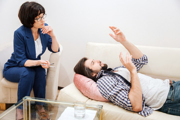 Man is lying on sofa and waving with his hands. He is quite emotional at the moment. He is talking to therapist. Woman is looking at man and listening to him very carefully.