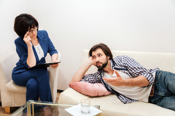 Man is lying on sofa in white room and talking to therapist. He is leaning on hand. Therapist is listening to him very carefully. She is holding one hand close to head.