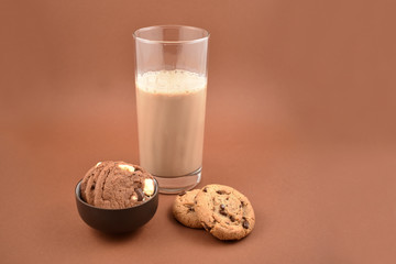Cookies with chocolate milk stock images. Biscuits on a brown background. Glass of chocolate milk with snack. glass of chocolate milk with biscuits