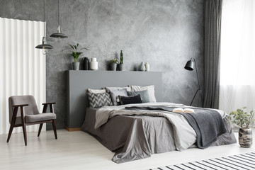 Modern grey bedroom interior with big bed with pillows and linen. Comfortable armchair next to the bed. Real photo.