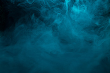 Colored turquoise smoke on a black background closeup